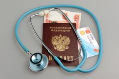 Stethoscope with passport, money and medical insurance policy on Royalty Free Stock Image