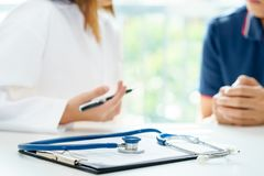Stethoscope on patient profile history form with doctor and patient are discussing, medical diagnosis concept. stock photos