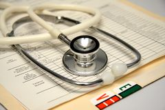 Stethoscope on a patients medical record. A stethoscope laying on a patients medical record folder stock photos
