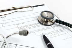 Stethoscope and pen on blank Patient information Stock Photography