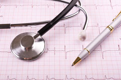 Stethoscope and pen on cardiogram Stock Images