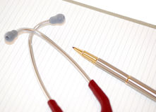 Stethoscope and pen on lined paper. A maroon stethoscope and gold/silver pen on lined paper. Can be used to signify medical paperwork Royalty Free Stock Images