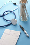 Stethoscope pen notepad and jar of sticks on doctors table Royalty Free Stock Photo