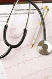 Stethoscope and pen over  questionnaire and cardiogram Stock Photo