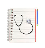 Stethoscope  with  pencil  on   notebook on white background Royalty Free Stock Photos