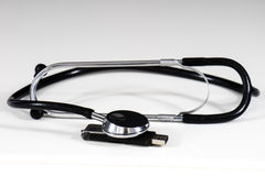 Stethoscope and pendrive. Flash drive and a stethoscope on a white table and black background Royalty Free Stock Image