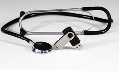 Stethoscope and pendrive. Flash drive and a stethoscope on a white table and black background Royalty Free Stock Photos