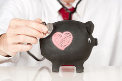 Stethoscope on a piggy bank Royalty Free Stock Images