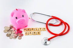 Stethoscope with piles of coins, red heart, piggy bank, saving f. Healthcare text word made with wood blocks on stethoscope with piles of coins, red heart, piggy Royalty Free Stock Photography