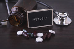 Stethoscope, pill bottle, Various pills, capsules and HEALTHY on wooden background with copyspace area. Stock Photos