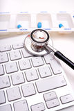Stethoscope, pill box and keyboard Stock Photo