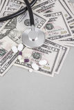 Stethoscope and pills on American Dollars Royalty Free Stock Image