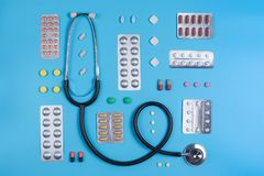 Stethoscope and pills in blisters on a blue background stock image