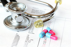 Stethoscope and pills on a check-up report Royalty Free Stock Photos