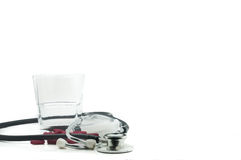 Stethoscope, pills and glass of water with white background Stock Photo