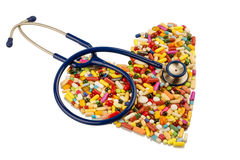 Stethoscope and pills in heart shape Stock Images