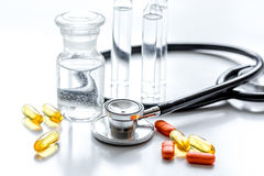Stethoscope, pills and mixture in medical room on white background Stock Images