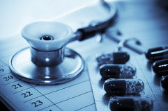 Stethoscope and pills over notebook Stock Photo