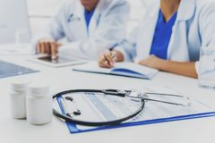 Stethoscope and Pills on Table. Docs on Background. Physicians on Consultation. Innovations in Medicine. Attractive Doctors. Clinic on Background. Healthcare stock image