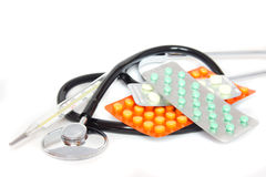 Stethoscope with pills and thermometer Stock Images