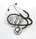 Stethoscope and pills on white Royalty Free Stock Photo