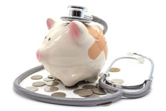 Stethoscope with pink piggy bank and coins Royalty Free Stock Image