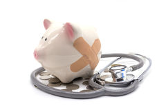 Stethoscope with pink piggy bank and coins Stock Images
