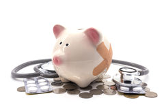 Stethoscope with pink piggy bank and coins Stock Photos