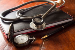 Stethoscope with pocket watch,book and pen Stock Images