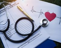 The Stethoscope put on the insurance claim form,beside cutted red heart paper and heart rate drawing ,on green grass ground floor. Vintage warm light tone royalty free stock photo