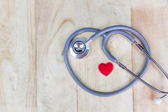 Stethoscope put on wooden background with heart red color.  Stock Image