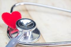 Stethoscope put on wooden background with heart red color.  Royalty Free Stock Image