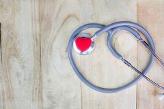 Stethoscope put on wooden background with heart red color.  Royalty Free Stock Photo