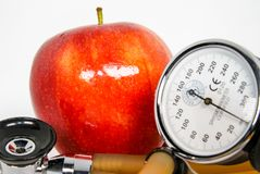 A Red Apple, Part of the Heart Healthy Team. A stethoscope, red apple and  blood pressure monitor are together as a team to defend against heart decease Royalty Free Stock Photo