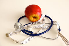 Stethoscope with red apples on a white background Royalty Free Stock Photo