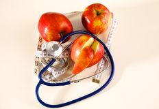 Stethoscope with red apples on a white background Stock Image