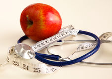 Stethoscope with red apples on a white background Royalty Free Stock Images