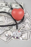 Stethoscope and red heart on American Dollars Royalty Free Stock Image