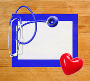 Stethoscope, red heart and blue clipboard over wooden Royalty Free Stock Image