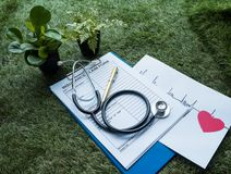 The Stethoscope and red heart with cardiogram of heart rate drawing on paper,with Insurance Claim Form. On green grass ground floor stock image