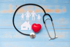 Stethoscope with Red heart shape, Family and House paper on blue pastel color wooden stock photos