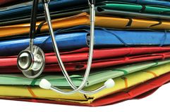 Stethoscope resting on a pile of folders stock photo