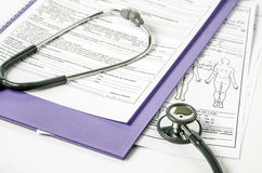 Stethoscope resting on a sheet of medical lab Royalty Free Stock Images