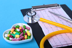 Stethoscope, RX prescription and colorful assortment pills and capsules on plate. Stock Image