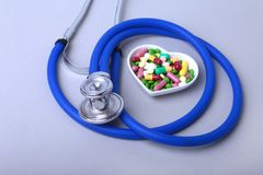 Stethoscope, RX prescription and colorful assortment pills and capsules on plate. Stock Photography