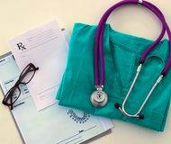 A stethoscope shaping a heart and a clipboard on a Stock Images