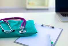 A stethoscope shaping a heart and a clipboard on a Stock Image