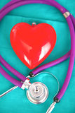 A stethoscope shaping a heart and a clipboard on a medical uniform, closeup Royalty Free Stock Image