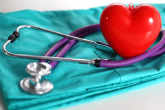 A stethoscope shaping a heart and a clipboard on a medical uniform, closeup Royalty Free Stock Images