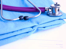A stethoscope shaping a heart and a clipboard on a medical uniform, closeup Royalty Free Stock Photography